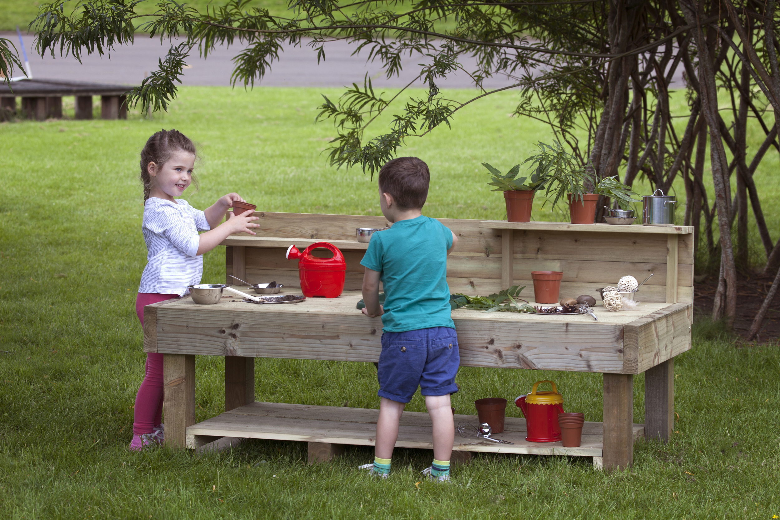 Two children demonstrating outdoor learning using a mud kitchen